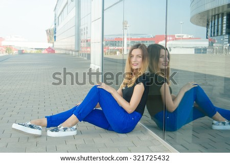Beautiful young red-haired girl in stylish blue trousers sitting on the tile near the building and looks directly