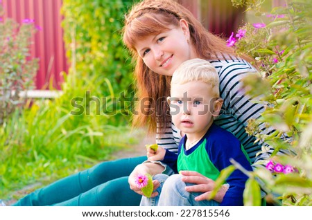 Beautiful young red-haired mother hugging her blond blue-eyed son, sitting next to the flower beds in the countryside. - stock photo