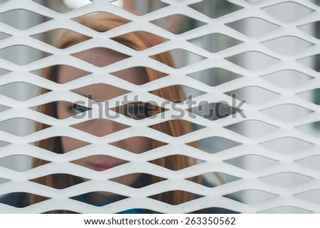Beautiful young redhead girl posing behind a grate. Intentionally out of focus. - stock photo