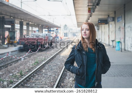 Beautiful young redhead girl posing in a railroad station - stock photo