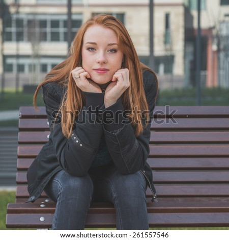 Beautiful young redhead girl posing in the city streets. Instagram style. soft focus - stock photo