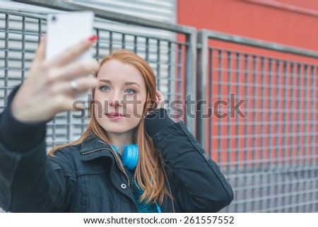 Beautiful young redhead girl taking a selfie in the city streets - stock photo