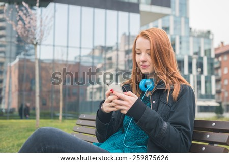 Beautiful young redhead girl texting on a bench in a city park - stock photo