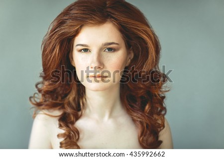 Beautiful young redhead woman with freckles portrait with curly hairdress - stock photo