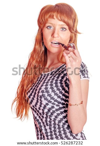 Beautiful young redhead woman with tobacco pipe on her mouth isolated on white