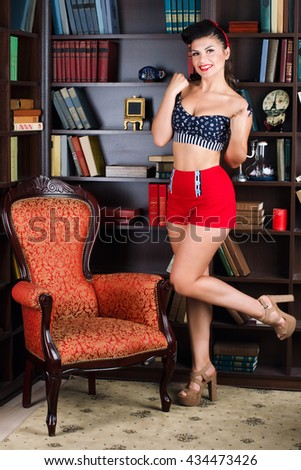 Beautiful young retro pinup woman reading book in the library