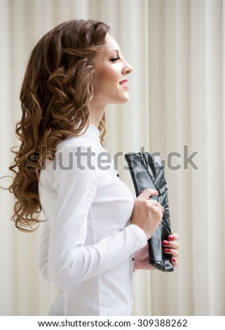 Beautiful young romantic elegant woman face, has brown eyes, haired nature hair, happy fun smile, hand with red manicure leather handbag, sexy lips. Pure makeup. White blouse.  Profile hairstyle - stock photo