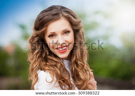 Beautiful young romantic elegant woman face, has brown eyes, haired nature hair, sexy red lips, white teeth, happy fun smile. Pure makeup. White blouse.  Green background day. Hairstyle. Lipstick - stock photo
