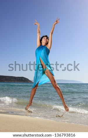 beautiful young russian woman at the beach with blue scarf - stock photo