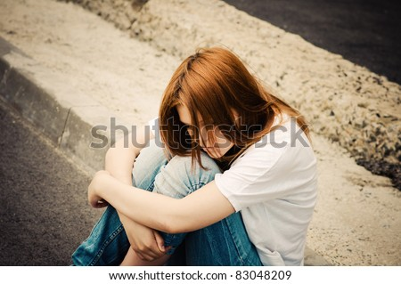 Beautiful young sad girl sitting on asphalt - stock photo
