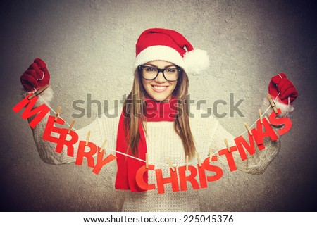 Beautiful young Santa woman with Merry Christmas decoration. Young teenage girl with glasses with knitted hat and scarf holding paper decor text smiling. Gray wall background. - stock photo