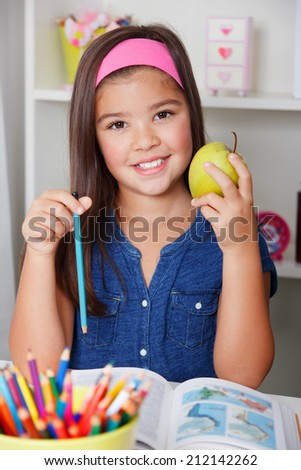 Beautiful young school girl eating an apple while learning