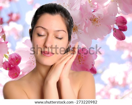 Beautiful young serene woman on floral background eyes closed - stock photo