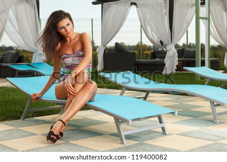 beautiful young sexy brunette girl sitting on chair next to a pool - stock photo