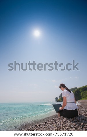 beautiful young sexy business woman with laptop at the sea