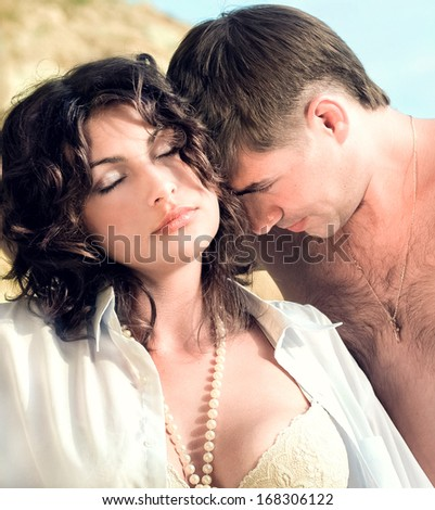 Beautiful young sexy couple on the beach - stock photo
