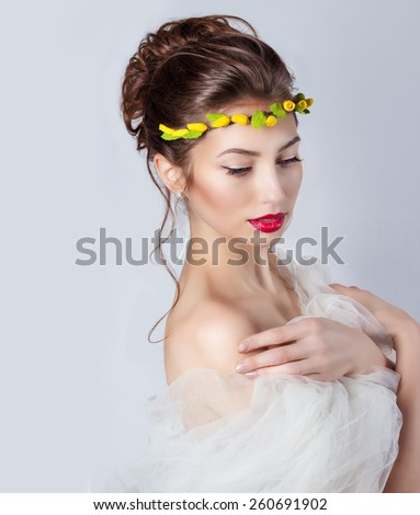 beautiful young sexy elegant woman with red lips, beautiful hair with a wreath of yellow roses on the head with bared shoulders, the way for the bride at a wedding - stock photo