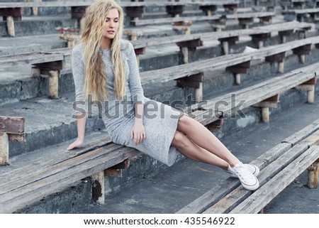 Beautiful young sexy girl in sneakers sitting on a bench at the stadium on a sunny day