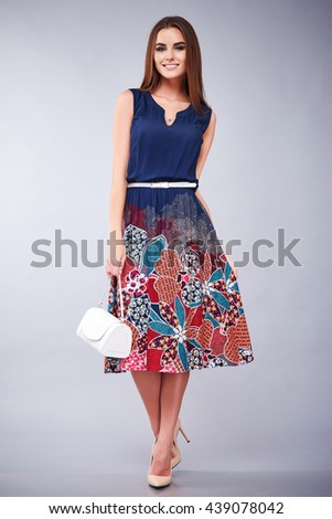 Beautiful young sexy girl with long brunette hair with a bright evening make-up perfect summer tan thin figure dressed in colored silk dress with handbag high heels shoes businesswoman casual clothes - stock photo