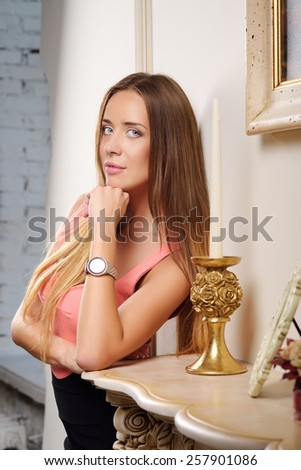 Beautiful young sexy girl with straight hair and big breasts in the interior of the hotel stands next to a marble fireplace and a chandelier - stock photo