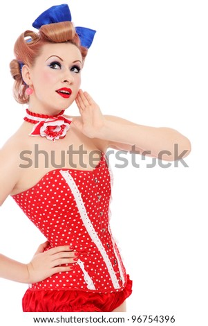 Beautiful young sexy pin-up promo girl in polka dot corset looking upwards with curious expression, on white background - stock photo