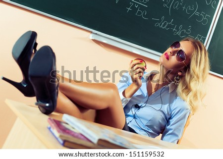 Beautiful young sexy teacher resting between the classes - stock photo