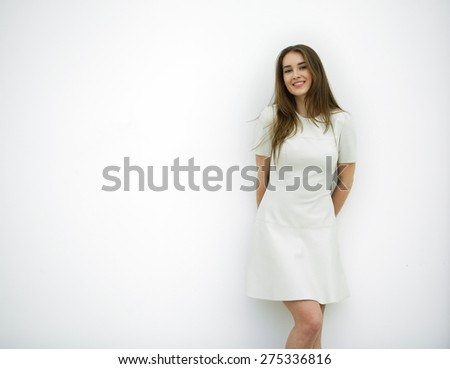 Beautiful young sexy woman in a light gray dress posing against a white wall - stock photo