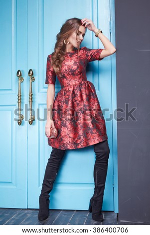 Beautiful young sexy woman lady in elegant evening dress red silk dress new stylish fashion collection season, long brown hair, shoes, interior blue door in the bedroom room meeting, party style brand - stock photo