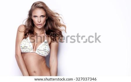 Beautiful young sexy woman posing in swimwear, looking at camera. Studio shot. White background. - stock photo