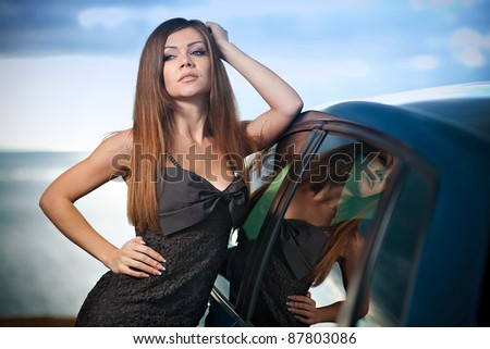 Beautiful young sexy woman standing near a car