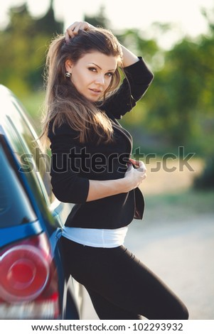 Beautiful young sexy woman standing near a car outdoor
