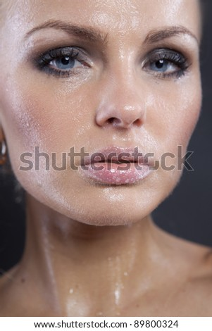 Beautiful young sexy woman with black eye make-up. Close-up face isolated on dark background