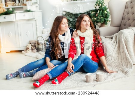 Beautiful young sisters twins teens. Christmas and New Year. Cosy holiday at the fireplace. Rustic decoration. Fireplace with books, candles and deer. Stylish Christmas. - stock photo