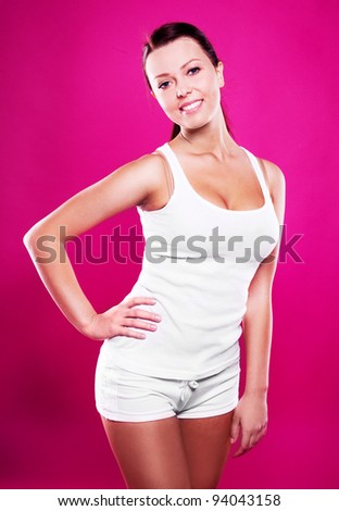 beautiful young slim brunette woman wearing white clothes, isolated against pink studio background