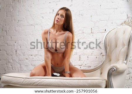 Beautiful young slim sexy girl with straight hair, big breasts and blue eyes in beige underwear with rhinestones on a leather sofa against a white brick wall - stock photo