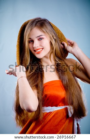 Beautiful young slim smiling woman in long orange dress and straw on blue background - stock photo