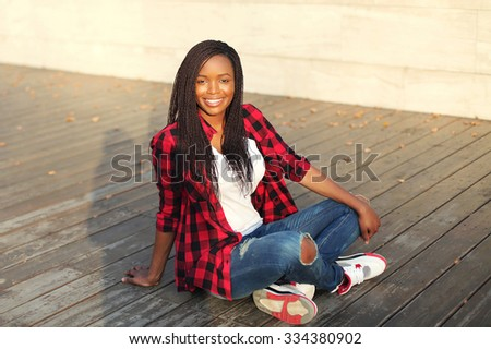 Beautiful young smiling african woman sitting in city evening - stock photo