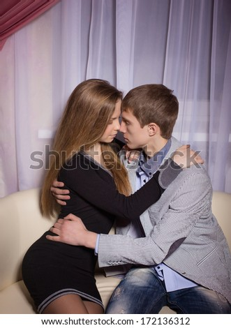 Beautiful young smiling couple in love embracing indoor - stock photo