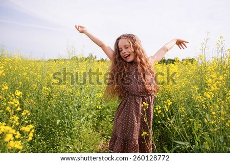 beautiful young smiling girl in a field of canola                               - stock photo