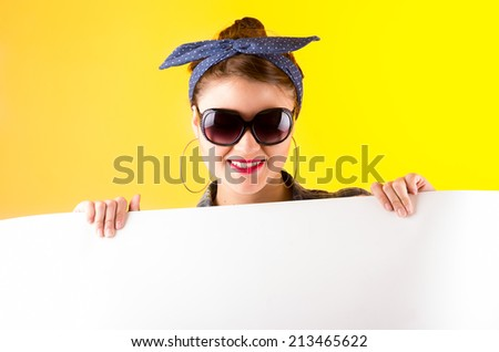 beautiful young smiling retro girl holding white paper over yellow background - stock photo