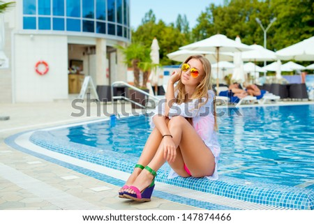 Beautiful young smiling woman sitting near pool