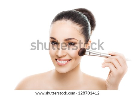 Beautiful young smiling woman with a makeup brush. Isolated on white background - stock photo