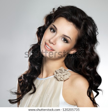 Beautiful young smiling  woman with long brown hair. Pretty model poses at studio.