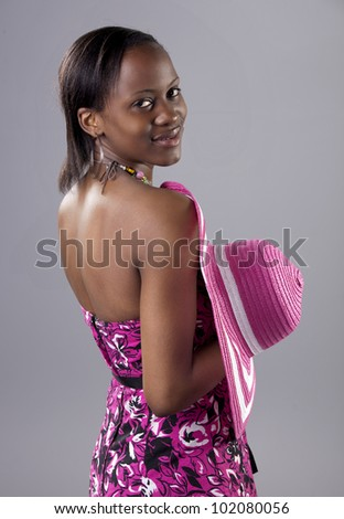 Beautiful young South African woman in bright colours looking back over her shoulder. - stock photo
