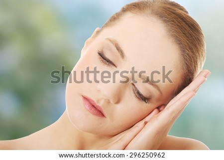Beautiful young spa woman with eyes closed.