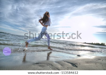 Beautiful young sport woman running on water at sea coast. Sunset with dramatic sky - stock photo
