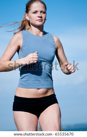 Beautiful young sport woman running over blue sky - stock photo