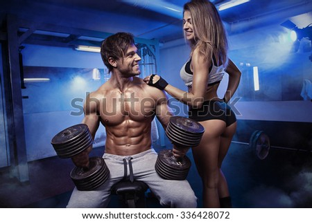 beautiful young sporty sexy couple showing muscle and workout in gym - stock photo