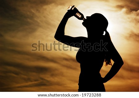 Beautiful young sporty woman drinking in front of a sunset. - stock photo
