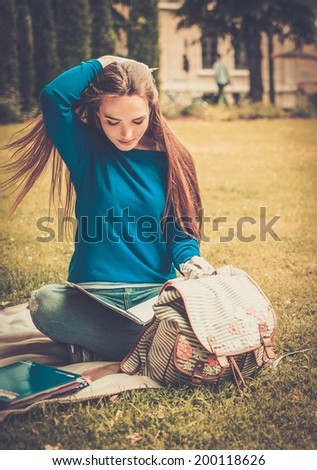 Beautiful young student girl in a city park on summer day - stock photo